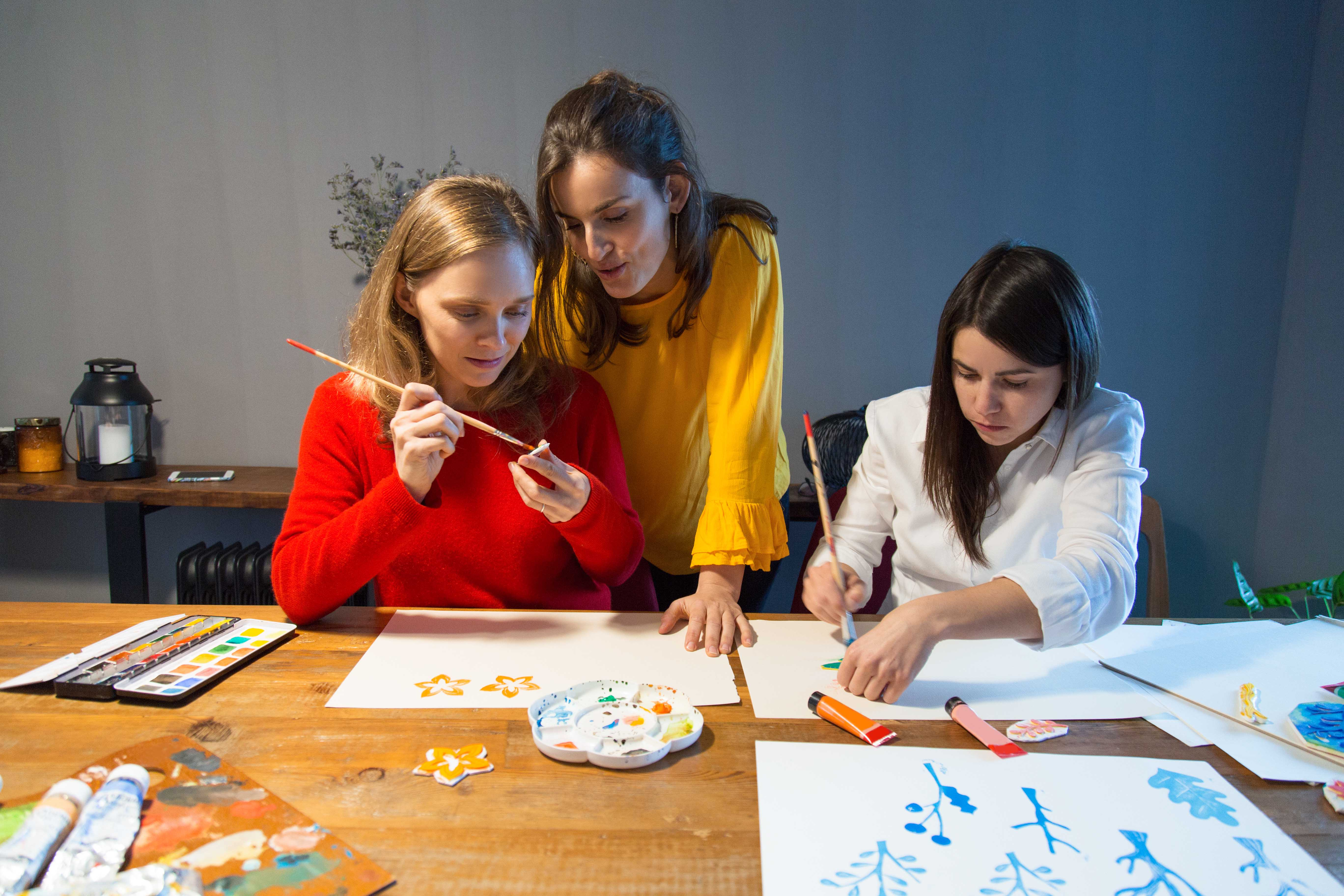 Drawing master supervising students work. Two girls painting with water colors, third one giving them advice. Panting class concept